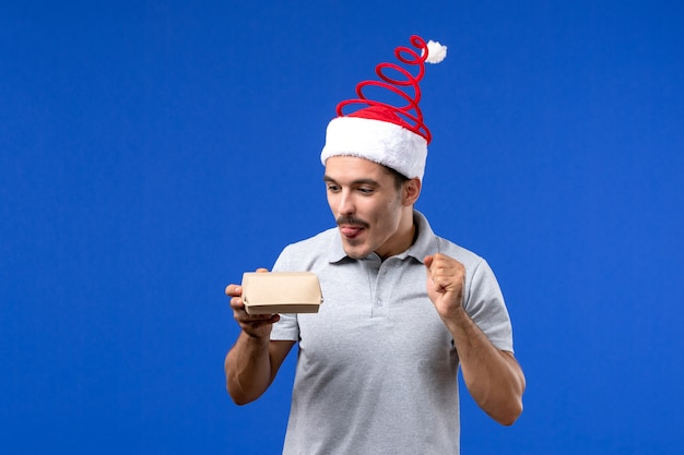 Vista frontale giovane maschio che tiene il pacchetto alimentare sulla parete blu lavoro maschio servizio di ristorazione gli esseri umani