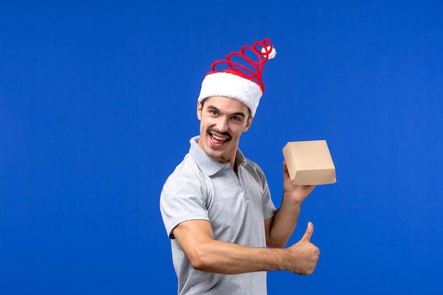 Vista frontale giovane maschio che tiene il pacchetto di cibo sul lavoro di servizio maschile di cibo da parete azzurro