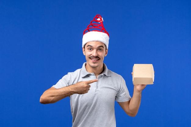 Вид спереди молодой мужчина держит пакет с едой на синей стене.