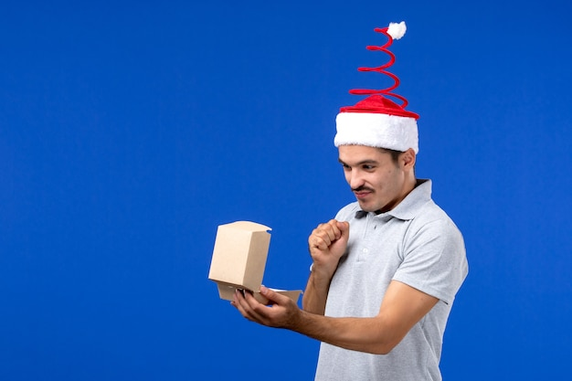 青い壁の男性のフードサービスの仕事でフードパッケージを保持している正面図若い男性