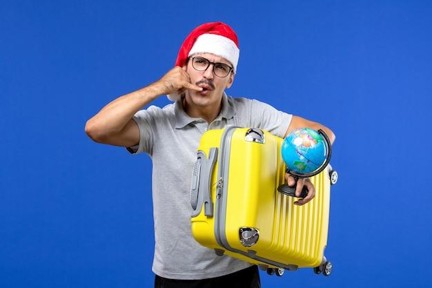 青い壁の飛行機の休暇旅行で地球儀と黄色のバッグを保持している若い男性の正面図