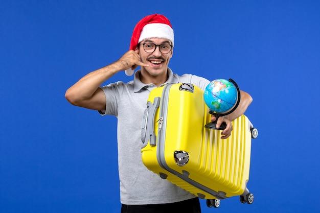 青い壁の飛行機の休暇旅行で地球儀と黄色のバッグを保持している正面図若い男性