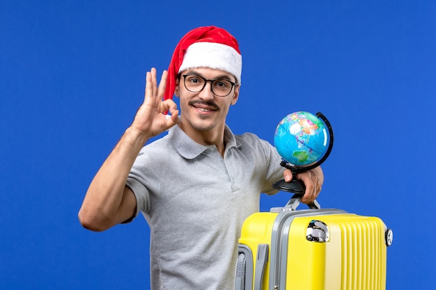 Front view young male holding globe and yellow bag on blue wall plane vacation trip