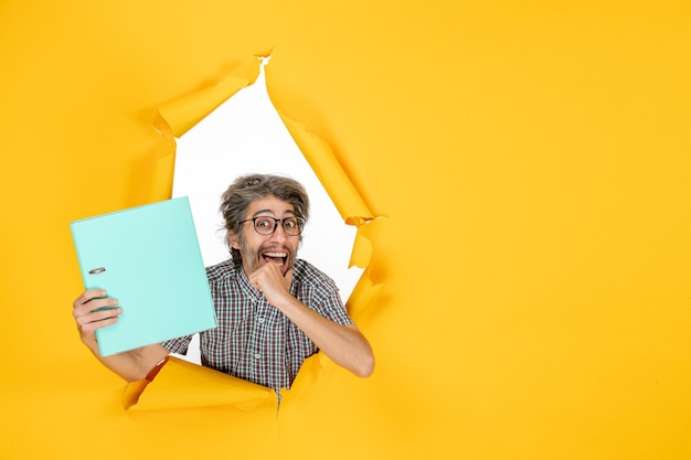 노란색 배경 색상 작업 사무실 감정 휴가 작업에 녹색 파일을 들고 전면 보기 젊은 남성