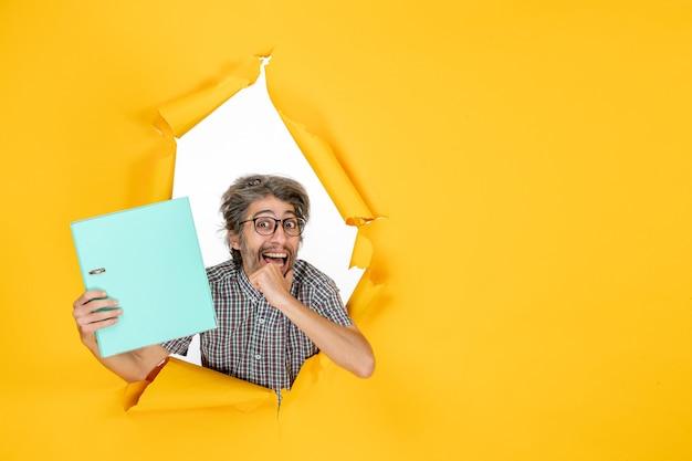Vista frontale giovane maschio che tiene file verde su sfondo giallo colore lavoro ufficio emozione vacanza lavoro