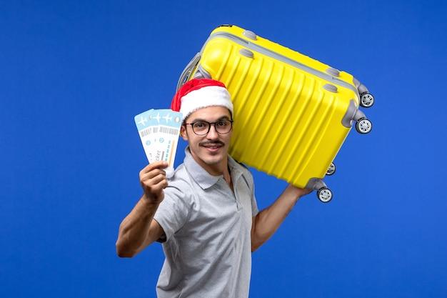 青い壁の飛行休暇の飛行機で重いバッグとチケットを保持している正面図若い男性