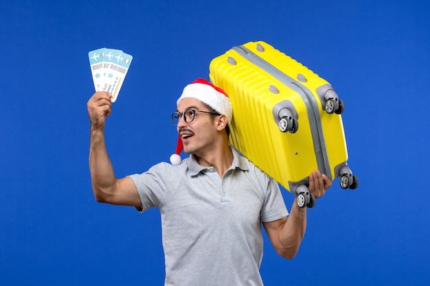Вид спереди молодого мужчины, держащего тяжелую сумку и билеты на самолетах для отпуска на синем полу