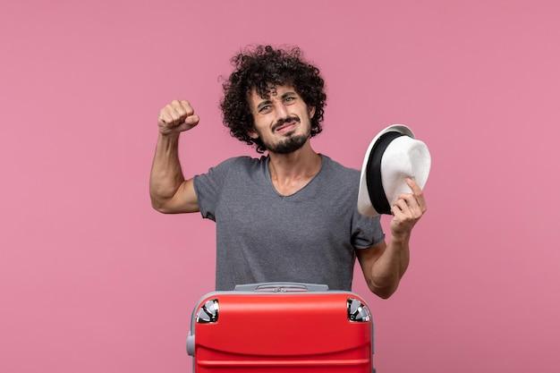 Vista frontale giovane maschio che tiene il cappello e si prepara per le vacanze sullo spazio rosa