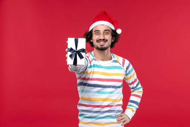 Вид спереди молодой мужчина держит праздничный подарок на красном столе новогодний праздник красные эмоции