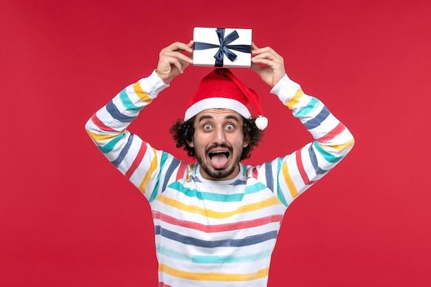 赤い壁の新年の休日の感情に休日のプレゼントを保持している若い男性の正面図