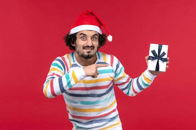 Вид спереди молодой мужчина держит праздничный подарок на красной стене новогодние праздники эмоции
