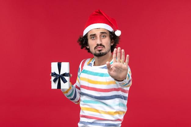 Вид спереди молодой мужчина держит праздничный подарок на красной стене новогодние праздники красные эмоции