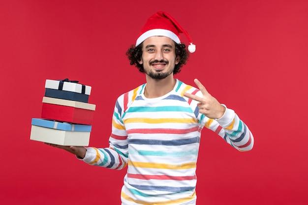 正面図若い男性が休日のプレゼントを明るい赤い壁の休日の新年の感情を保持しています