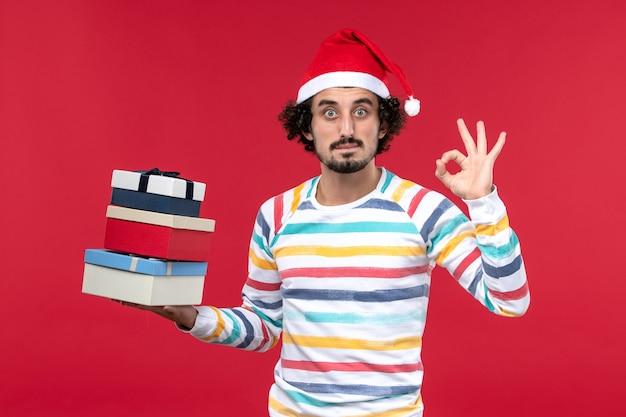 Вид спереди молодого мужчины, держащего праздничные подарки на красном столе, праздничная новогодняя эмоция