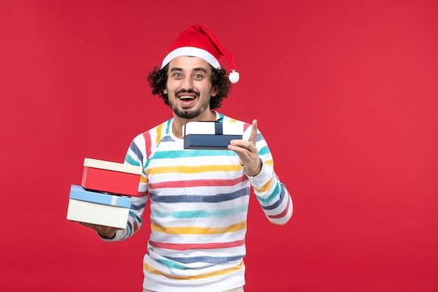 Вид спереди молодой мужчина держит праздничные подарки на красном столе новогодняя эмоция красный