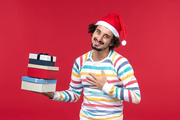 휴일을 들고 전면보기 젊은 남성 붉은 벽 새 해 휴일 감정에 선물
