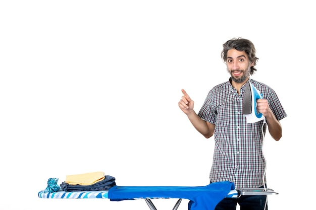 전면보기 흰색 배경에 철을 들고 젊은 남성 집 남자 색상 깨끗한 옷 다림질 가사 기계