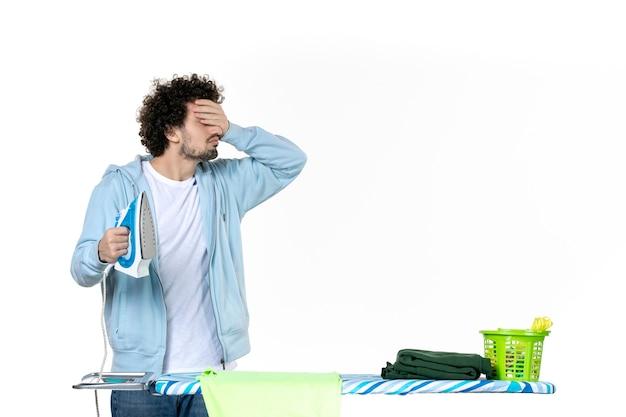 전면보기 젊은 남성 흰색 배경에 철을 들고 가사 색상 세탁 옷 청소 감정 남자