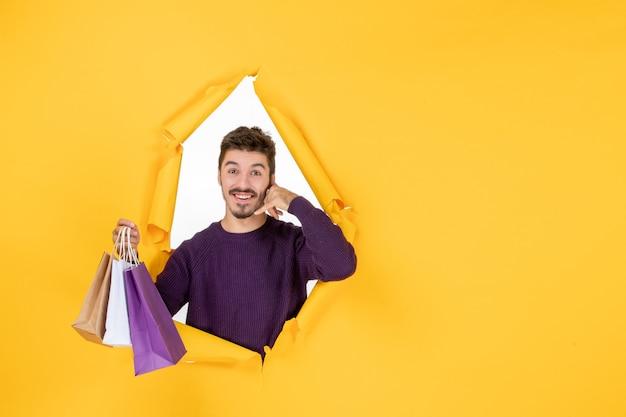 노란색 배경 모델 선물 새해 선물로 쇼핑한 후 작은 패키지를 들고 있는 전면 보기 젊은 남성은 크리스마스 색상을 제공합니다.