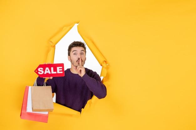 正面図黄色の背景に小さなパッケージとセールの書き込みを保持している若い男性新年現在の色休日ギフトクリスマス