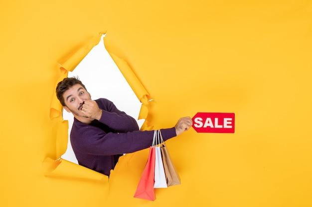 Вид спереди молодой мужчина, держащий маленькие пакеты и распродажу на желтом фоне, фото подарки, рождественские праздники, покупки, цвет