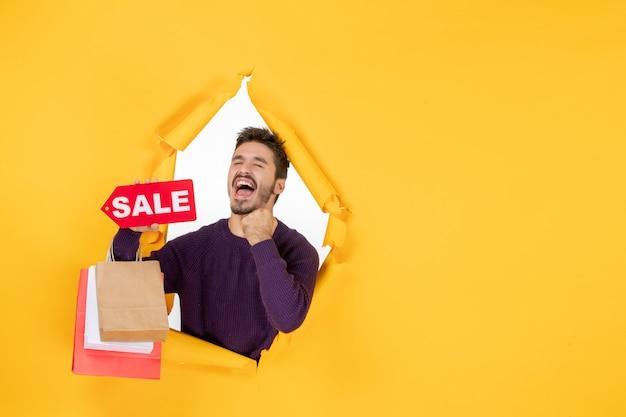 小さなパッケージを保持し、黄色の背景色の休日プレゼントショッピングギフトクリスマスに喜んで販売を書いている正面図若い男性