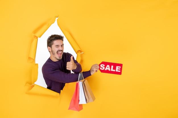 Vista frontale giovane maschio che tiene piccoli pacchetti e vendita scrivendo su sfondo giallo colore soldi shopping natalizio regalo foto