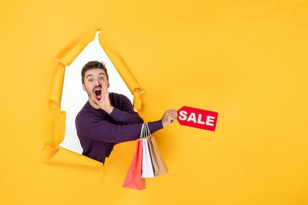 Vista frontale giovane maschio che tiene piccoli pacchetti e vendita scrivendo su sfondo giallo colore soldi foto natale vacanze shopping regali