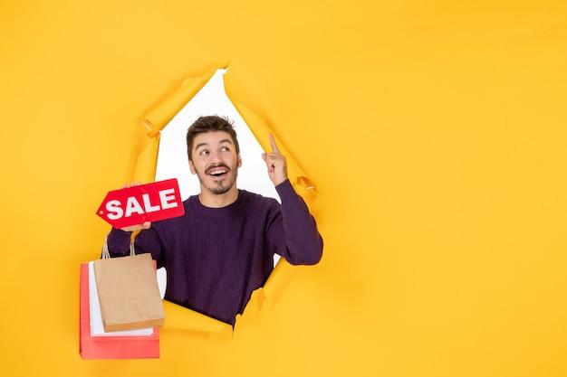 Vista frontale giovane maschio che tiene piccoli pacchetti e vendita scritta su sfondo giallo colore capodanno regali shopping regalo natale