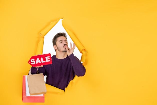Vista frontale giovane maschio che tiene piccoli pacchetti e vendita scritta su sfondo giallo colori capodanno regalo vacanza natale