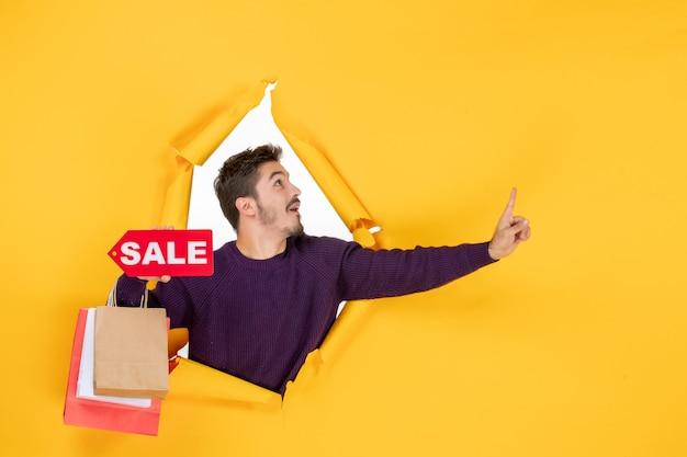 Vista frontale giovane maschio che tiene piccoli pacchetti e vendita scrivendo su sfondo giallo regalo colore vacanza foto shopping