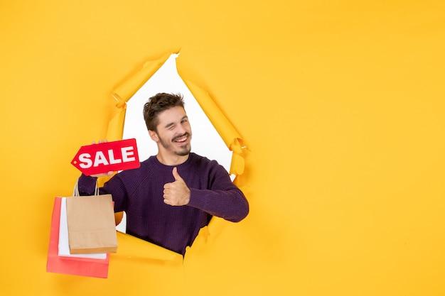 Vista frontale giovane maschio che tiene piccoli pacchetti e vendita scrivendo su sfondo giallo regalo di festa di colore del nuovo anno natale