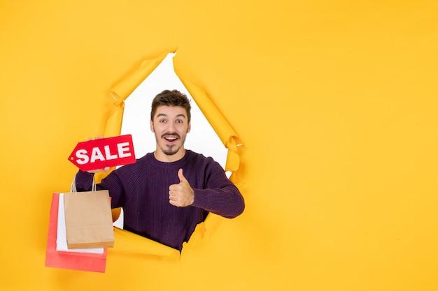 Vista frontale giovane maschio che tiene piccoli pacchetti e vendita scritta su sfondo giallo anno nuovo presente colore regalo di natale natale