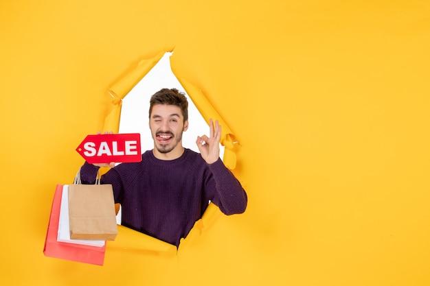 Vista frontale giovane maschio che tiene piccoli pacchetti e vendita scritta su sfondo giallo anno nuovo presente colore regali per le vacanze natale