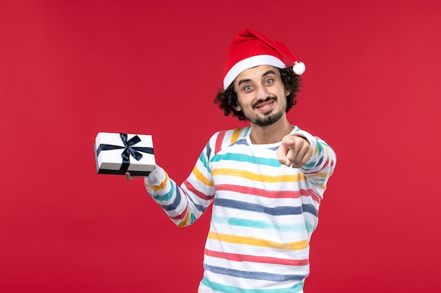 Вид спереди молодой самец держит маленький подарок на красном столе эмоции праздников новый год