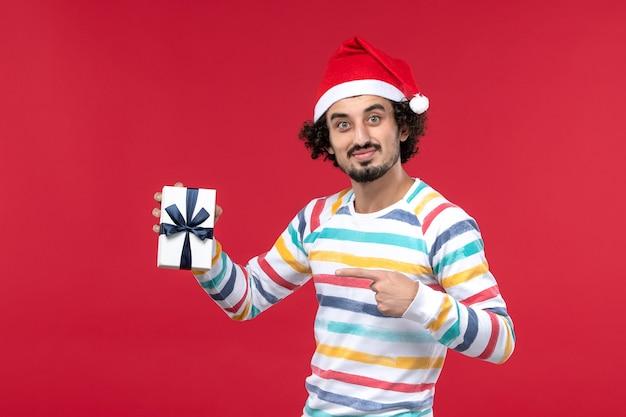 Вид спереди молодой самец, держащий маленький подарок на красном столе, праздничная новогодняя эмоция