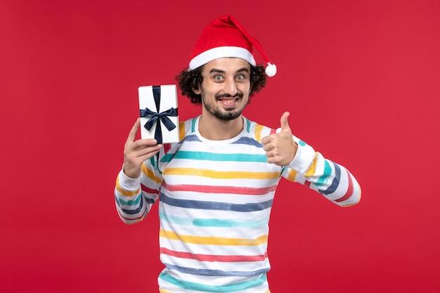 Вид спереди молодой мужчина держит маленький подарок на красном столе красный праздник новогодняя эмоция