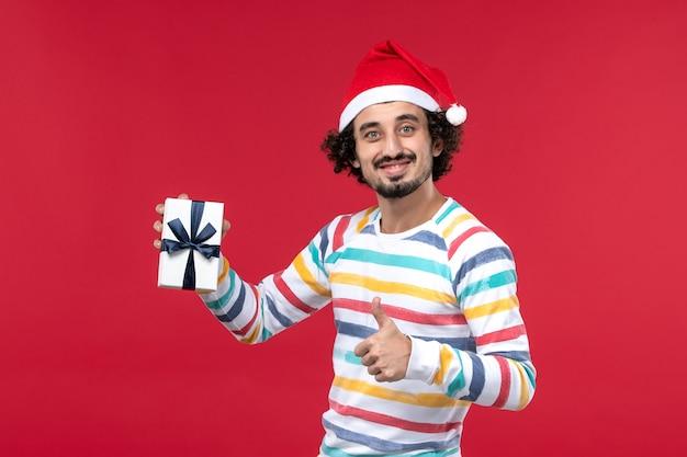 赤い壁の感情休日新年にほとんどプレゼントを保持していない正面図若い男性