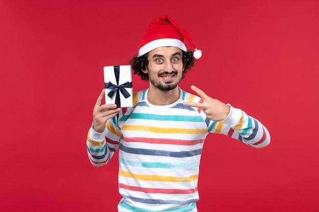 Вид спереди молодой мужчина держит маленький подарок на красной стене праздник новогодние эмоции красный