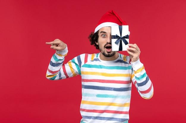 赤い壁にほとんどプレゼントを持っていない正面図若い男性新年の休日の感情赤