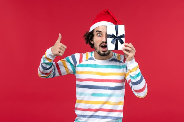Вид спереди молодой мужчина держит маленький подарок на красной стене новогодние праздники эмоция красный