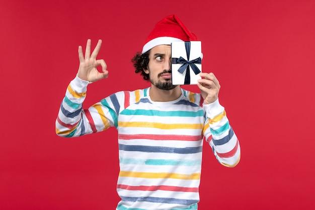 Вид спереди молодой мужчина держит маленький подарок на красной стене новогодние праздники эмоции красный