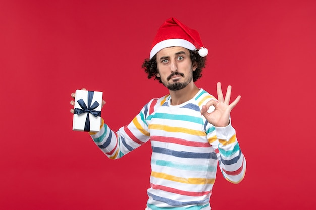 Front view young male holding little present on red wall emotion holidays new year