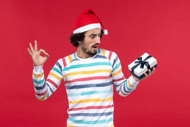 Giovane maschio di vista frontale che tiene poco presente sull'emozione del nuovo anno di feste della parete rossa