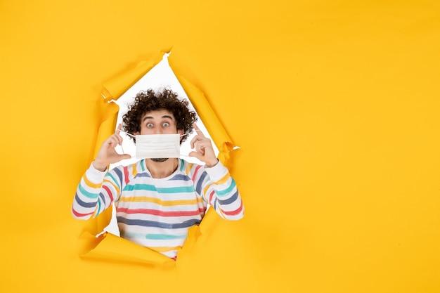 Вид спереди молодого мужчины, держащего маску на желтом здоровье, коронавирус, коронавирус, человеческое фото, цвета пандемии
