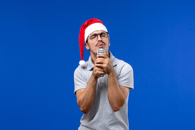 Front view young male holding mic on the blue wall new year singer music male