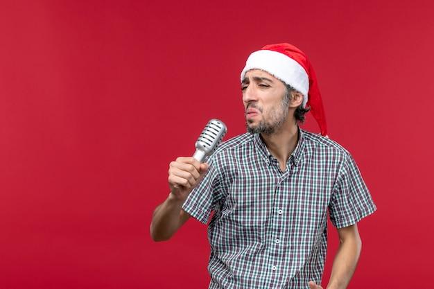 Вид спереди молодой мужчина держит микрофон на красном фоне