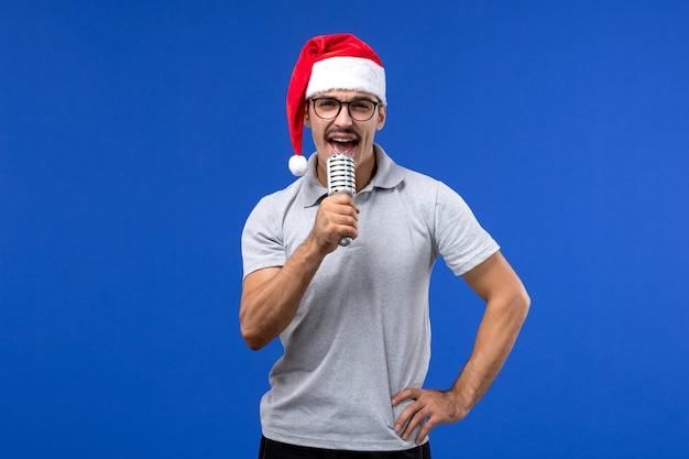 青い壁にマイクを保持している正面図若い男性新年の歌手音楽男性