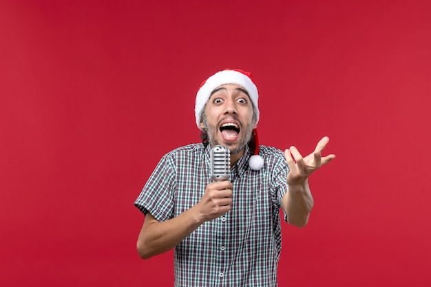 Front view young male holding mic on a red background
