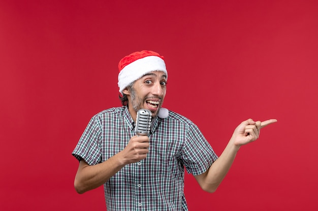 Front view young male holding mic on red background